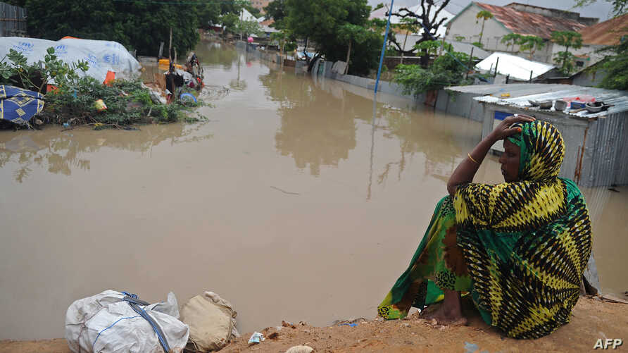 A woman living at a camp for the internally displaced sits on high ground above a flooded street on May 20, 2018 in Mogadishu after temporary shelters were inundated in Somalia's capital following heavy overnight rainfall.