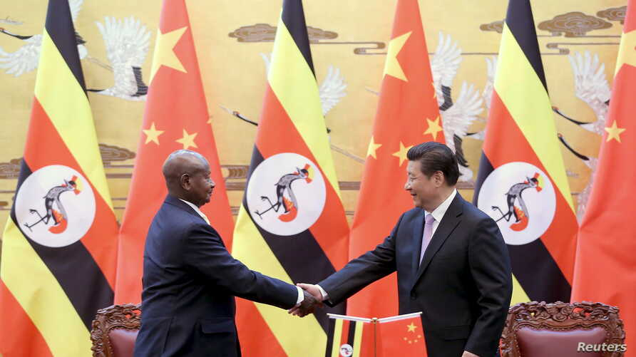 FILE - Ugandan President Yoweri Kaguta Museveni, left, shakes hands with Chinese President Xi Jinping during a signing ceremony in the Great Hall of the People in Beijing, March 31, 2015.