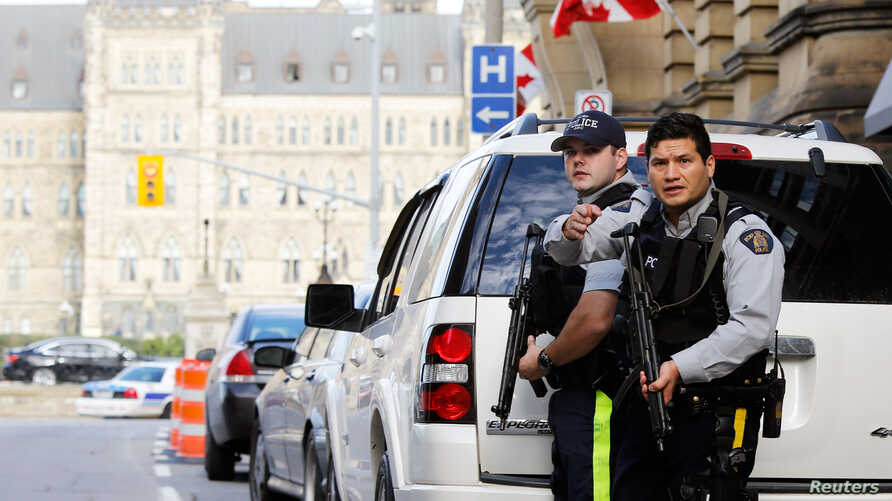 FILE - Armed RCMP officers guard access to Parliament Hilll following a shooting incident in Ottawa.