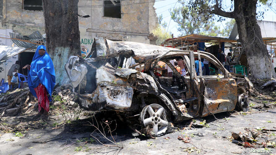 A Somali woman looks at the wreckage of a vehicle near the scene of an explosion in Mogadishu, Somalia, March 7, 2019.