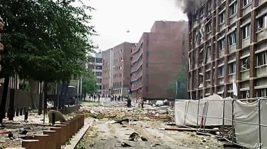 In this video image taken from television, smoke is seen billowing from a damaged building as debris is strewn across the street after an explosion in Oslo, Norway, Friday, July 22, 2011