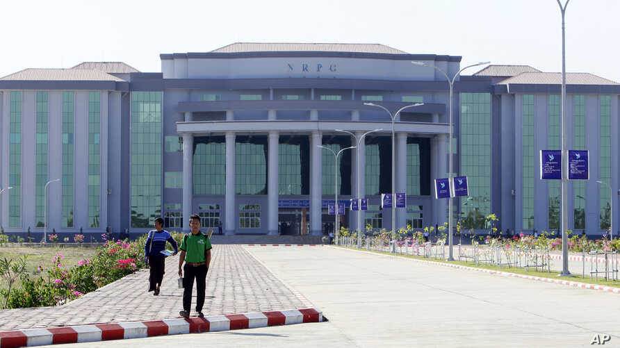 Pedestrians walk in front of the National Reconciliation and Peace Center building in Nay Pyi Taw as State Counsellor Daw Aung San Suu Kyi holds talks with representatives of the non-signatories to the country's Nationwide Ceasefire Agreement in Nay