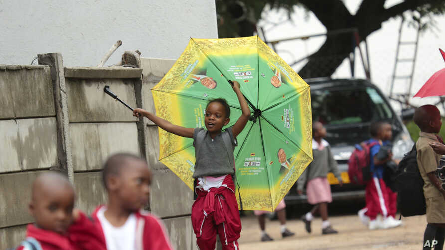 A child plays with an umbrella bearing the portrait of Zimbabwean President Emmerson Mnangagwa, at a public school in Harare, Feb. 5, 2019.