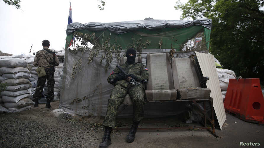 Pro-Russian fighters man a checkpoint in the eastern Ukrainian city of Donetsk, July 7, 2014.