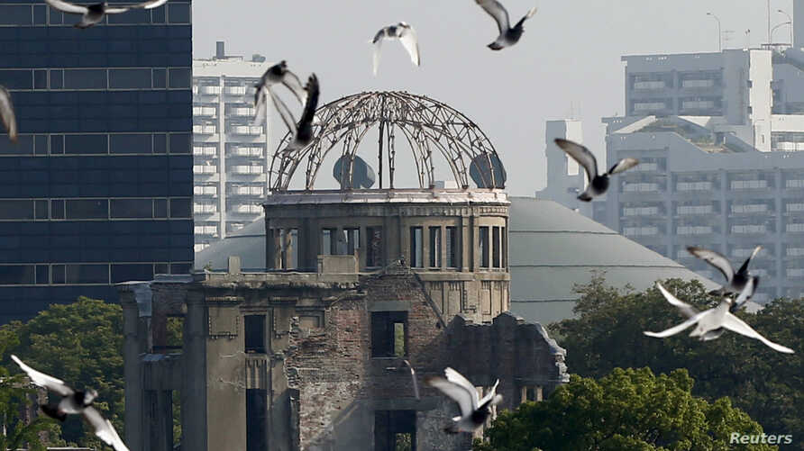 Doves fly over Peace Memorial Park with Atomic Bomb Dome in the background, at a ceremony in Hiroshima, August 6, 2015.