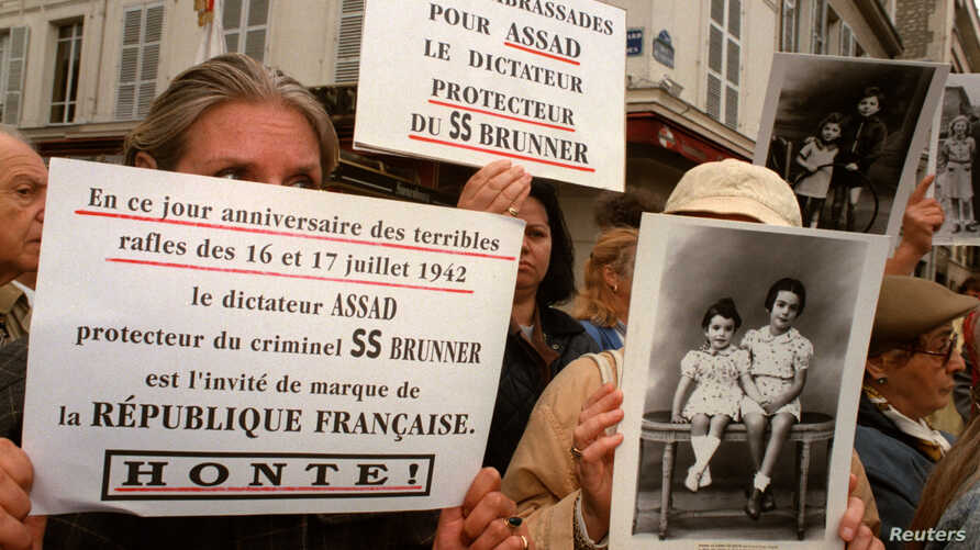 FILE - A few dozen members of Jewish organizations express outrage that Syrian President Hafez al-Assad, whom they accuse of sheltering convicted Nazi criminal Alois Brunner, was to be received by French President Chirac on the anniversary of a WWII
