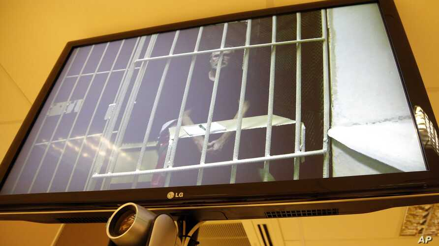Greenpeace International activist and the Arctic Sunrise ship radio operator Colin Russell of Australia is shown behind bars on a TV screen during a court hearing in St.Petersburg, Russia, Nov. 28, 2013.