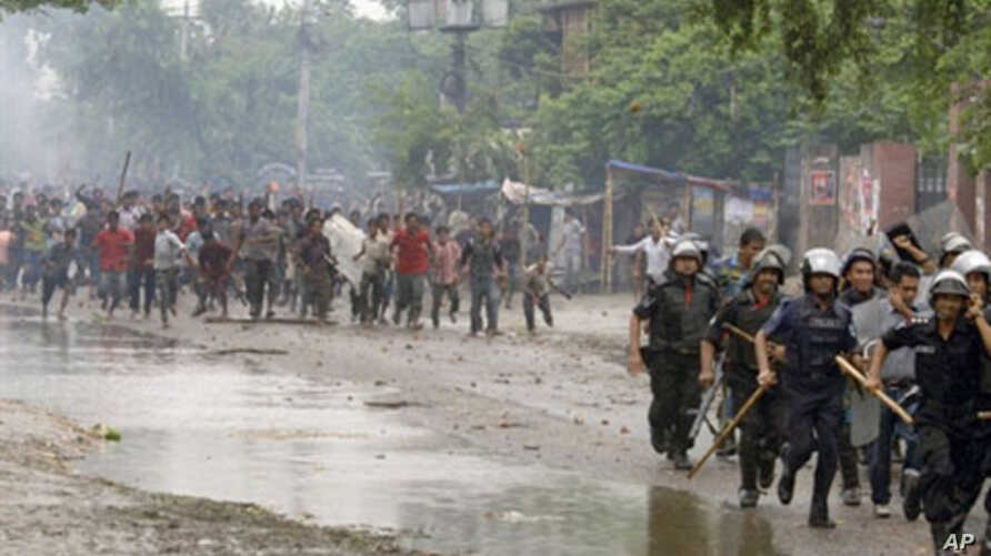 Bangladeshi policemen run from garment workers on a highway during clashes between garment workers and police in Asulia, some 20kms north-west of Dhaka, 31 Jul 2010
