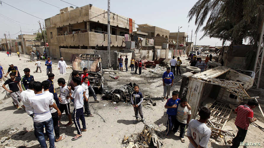 Iraqi residents gather at the site of a car bomb attack in the Kamaliya district in Baghdad, April 15, 2013.