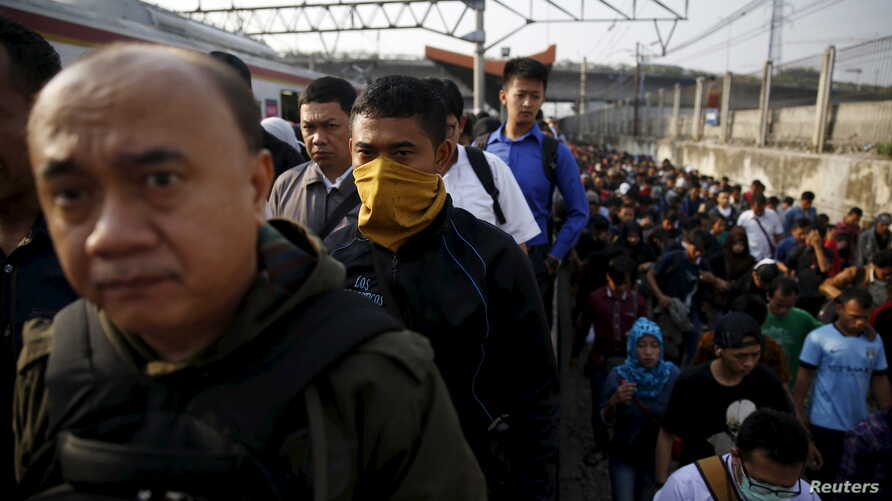FILE - Indonesia workers walk through train tracks as they go to work at Tanah Abang train station in Jakarta, Oct. 15, 2015. An Indonesian presidential decree requires all employers to provide language training in Bahasa Indonesia to foreign workers