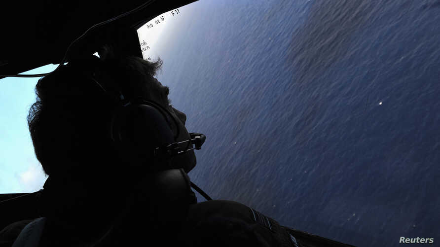 Co-pilot and Squadron Leader Brett McKenzie looks from the cockpit of a Royal New Zealand Air Force aircraft as they fly over the southern Indian Ocean, to continue the search for Flight MH370, April 13, 2014.