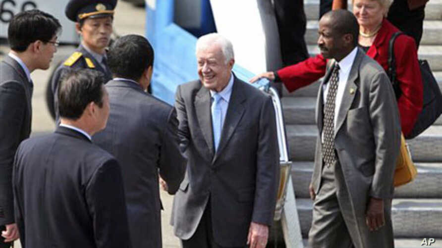 Former U.S. President Jimmy Carter, accompanied by his delegation members, is greeted upon arrival in Pyongyang, North Korea,  April 26, 2011