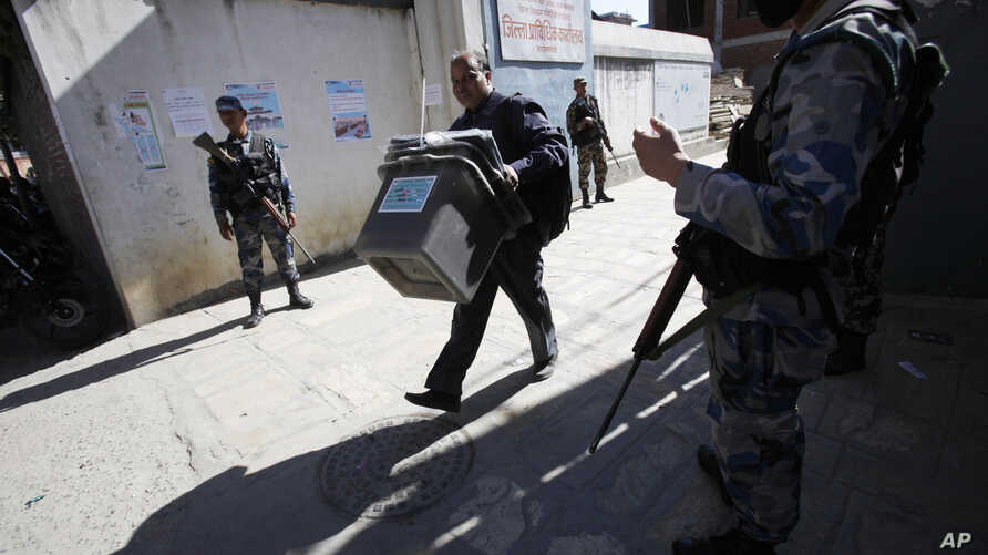 A Nepal election commission officer carrying ballot boxes heads to a polling booth in Katmandu, Nov. 17, 2013.