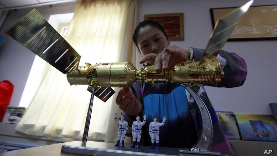 A vendor assembles a model showing the Shenzhou 9 space craft docked with the Tiangong 1 space module with three astronauts, June 17, 2012.