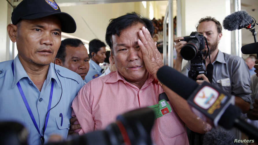 Soum Rithy, center, who lost his father and three siblings during Khmer Rouge regime, is escorted as he cries after the verdict was delivered in the trial of former Khmer Rouge head of state Khieu Samphan and former Khmer Rouge leader  Nuon Chea at t