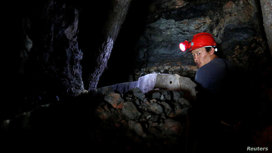 FILE - Uuganbaatar works on extracting coal from a primitive mine in Nalaikh, one of the nine districts of Mongolian capital Ulaanbaatar, Mongolia, June 29, 2017.