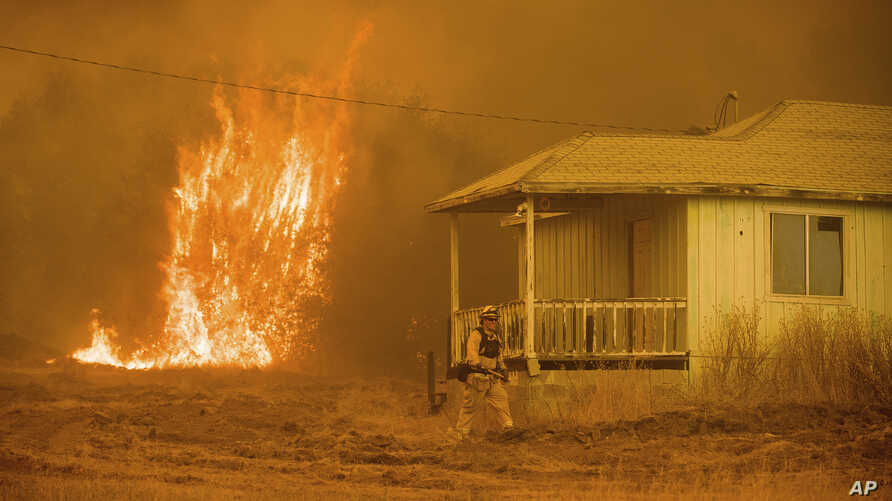 Flames rise behind a vacant house as a firefighter works to halt a wildfire near Mariposa, Calif., July 19, 2017. The California blaze in the rugged mountains outside of Yosemite National Park forced thousands of nearby residents to flee their homes....