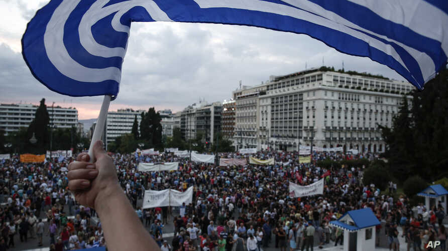 A protester waves a Greek flag during an anti-austerity rally in front of the parliament building in Athens, Greece, June 21, 2015.