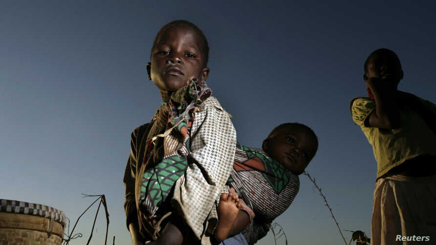 A young girl carries her sister through a cornfield in Masongo village outside Lilongwe, Malawi, May 13, 2008.