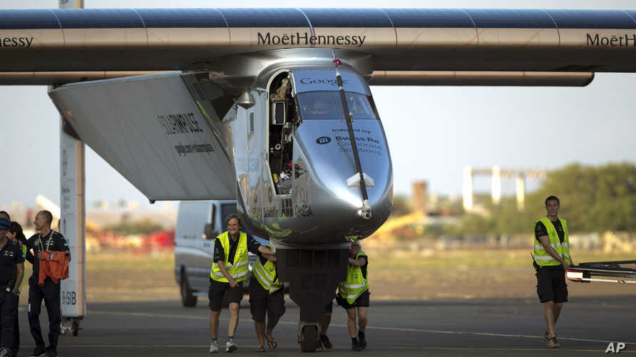 FILE - In this July 3, 2015, file photo, ground crew push the Solar Impulse 2, a solar powered airplane, towards the hangar after landing at the Kalaeloa Airport in Kapolei, Hawaii.