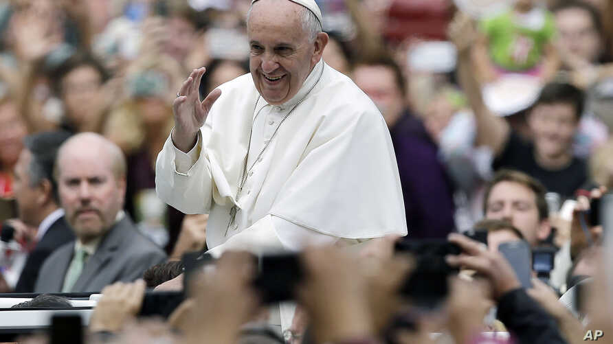 Pope Francis acknowledges faithful as he parades on his way to celebrate Mass in Philadelphia, Sept. 27, 2015.