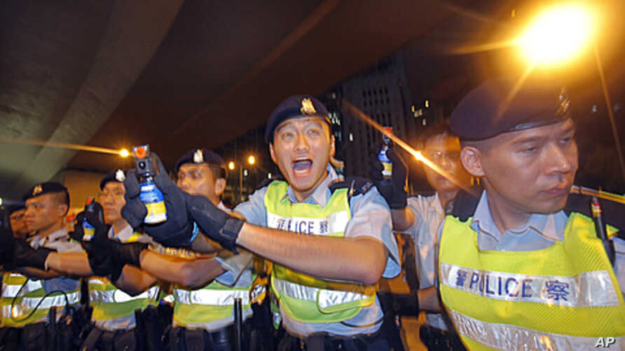 Police officers hold pepper spray cans against protesters as they try to break through a police cordon to carry out a sit-in protest in the Hong Kong's central business district, July 1, 2011.