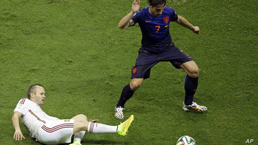 Spain's Andres Iniesta tries to reach the ball against Netherlands' Daryl Janmaat during the group B World Cup soccer match between Spain and the Netherlands at the Arena Ponte Nova in Salvador, Brazil, June 13, 2014.