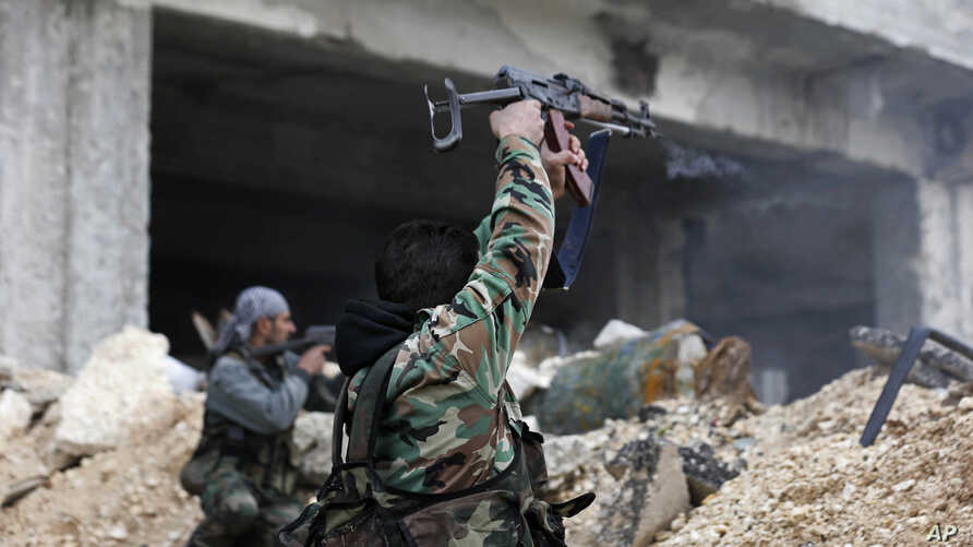 Syrian soldiers fire their weapons during a battle with rebel fighters at the Ramouseh front line, east of Aleppo, Syria, Dec. 5, 2016.