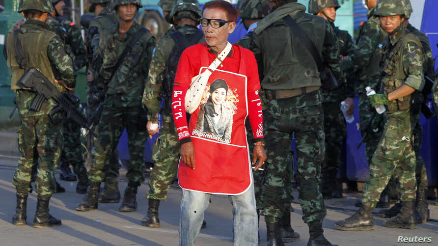 A member of the pro-government 'Red Shirt' group walks past Thai soldiers on the outskirts of Bangkok on May 22, 2014.