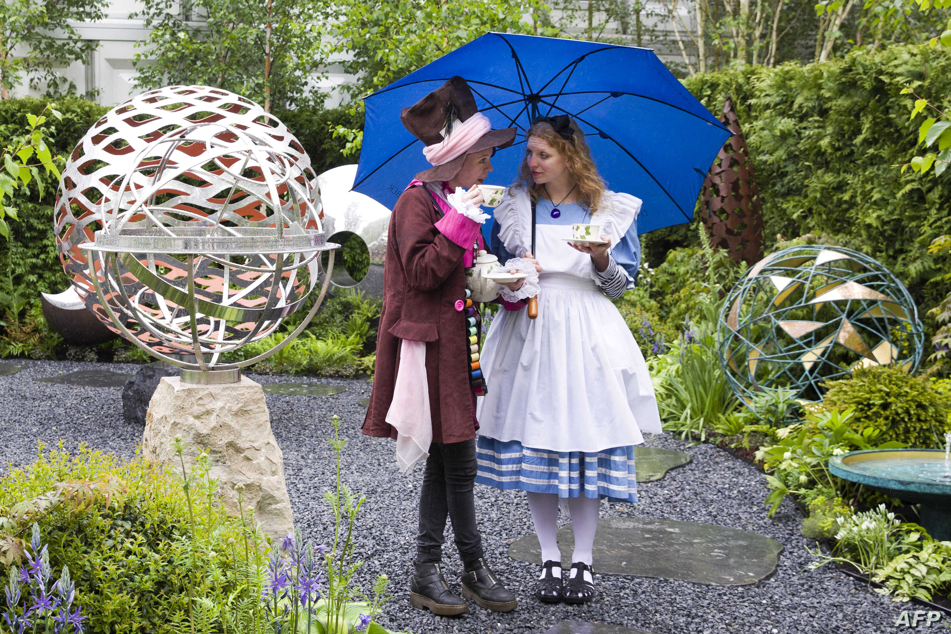 """FILE - Exhibitors dressed as """"The Hatter"""" (L) and """"Alice in Wonderland"""" (R) drink tea whilst sheltering from the rain under an umbrella on the David Harbor stand at the 2015 Chelsea Flower Show in London, May 18, 2015."""