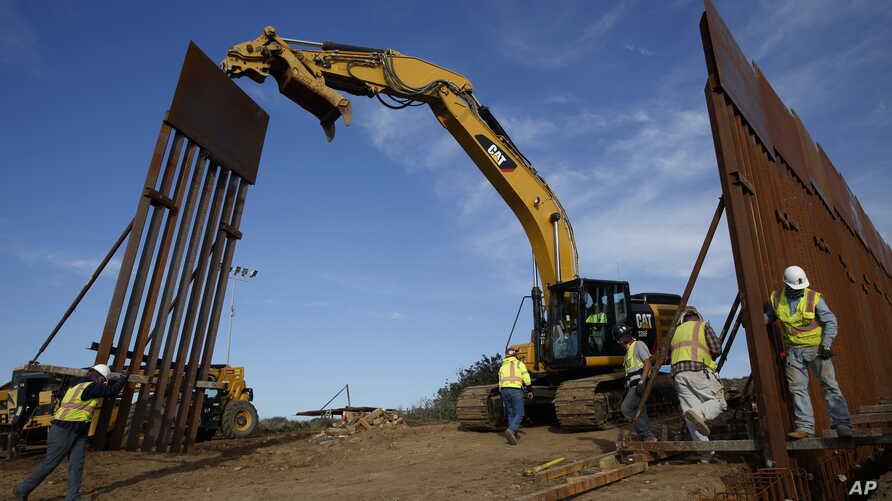 FILE - Construction crews install new border wall sections, Jan. 9, 2019, seen from Tijuana, Mexico.