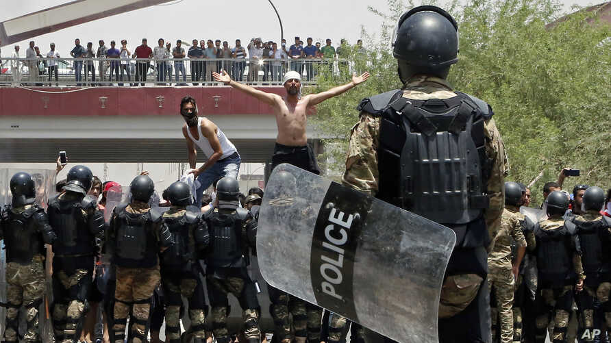 FILE - Iraqi riot police prevent protesters from storming the provincial council building during a demonstration in Basra, 340 miles (550 km) southeast of Baghdad, Iraq, July 15, 2018.