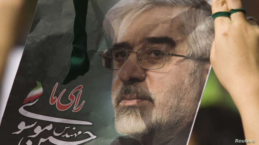 An Iranian woman holds a picture of defeated presidential candidate and opposition leader Mirhossein Mousavi during a rally marking Qods (Jerusalem) Day in Tehran, September 18, 2009.