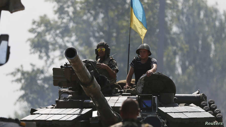 Ukrainian soldiers look out from a tank at a position some 60 km from the eastern Ukrainian city of Donetsk, July 10, 2014.
