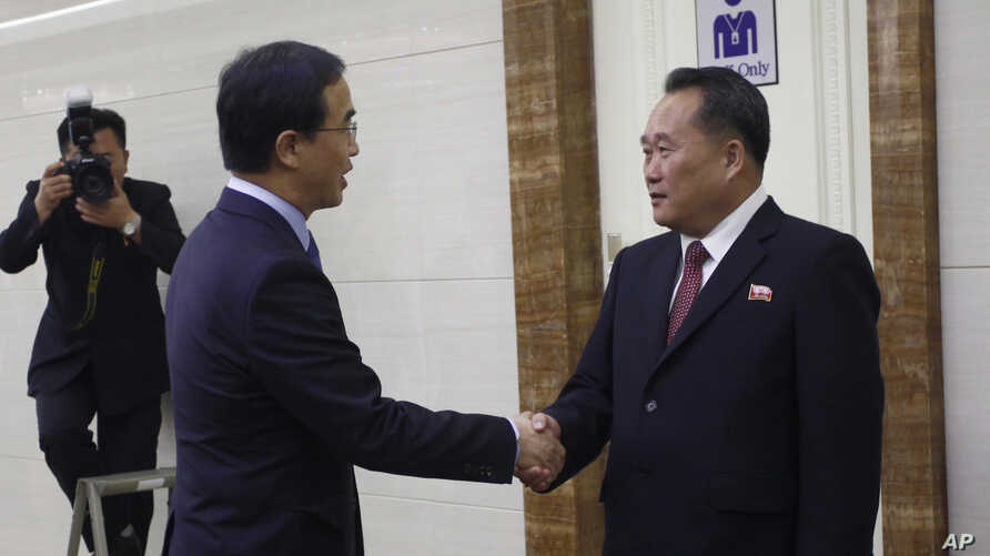 Ri Son Gwon, right, chairman of the North's Committee for the Peaceful Reunification of North Korea, shakes hands with South Korean Unification Minister Cho Myoung-gyon at the Pyongyang Airport in Pyongyang, North Korea, Oct. 4, 2018. The delegation