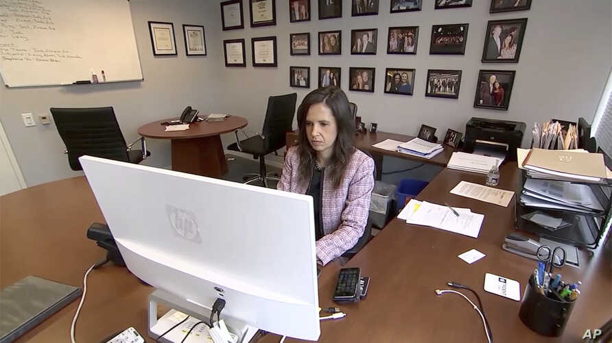 In this Dec. 4, 2017, image made from a video, Eleanor McManus works at her desk at Trident DMG, the Washington public relations firm she co-founded.