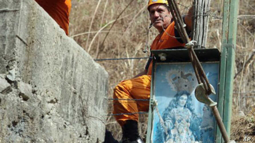A rescue worker looks on outside the Minesadco mine in Portovelo, southern Ecuador. A tunnel collapsed in the gold mine, operated by the Ecuadorean company Minesadco, trapping four miners 490 feet, some 150 meters, underground, 16 Oct 2010