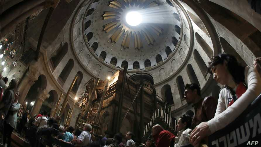 A picture taken with a fisheye lens shows Christian worshippers praying inside the Church of the Holy Sepulchre as rays of sunlight come through the top rotunda in Jerusalem's Old City during the Good Friday procession on March 25, 2016.