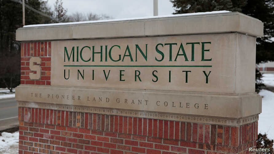 FILE: A sign for Michigan State University is seen near the campus in East Lansing, Michigan,  Feb. 1, 2018.