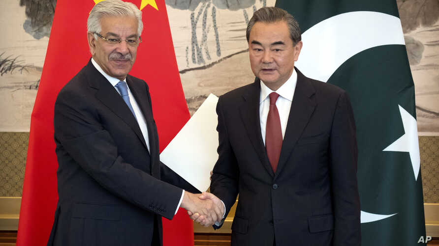 Pakistan's Foreign Minister Khawaja Muhammad Asif, left, and Chinese Foreign Minister Wang Yi shake hands at the end of a joint press conference at the Diaoyutai State Guesthouse in Beijing, Sept. 8, 2017.
