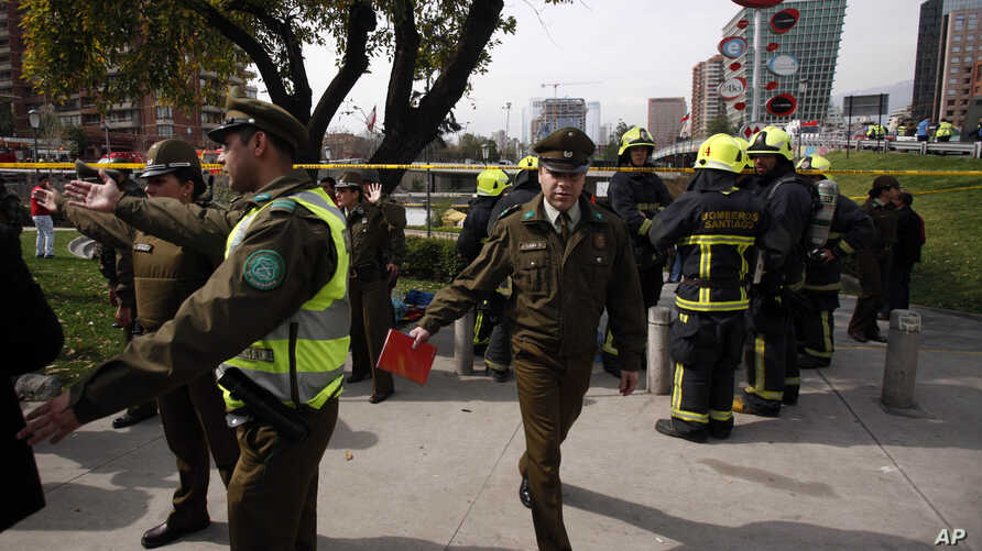 Police officer direct the curious away from a blast site as fire fighters stand by, at a subway station in Santiago, Chile, Sept. 8, 2014.