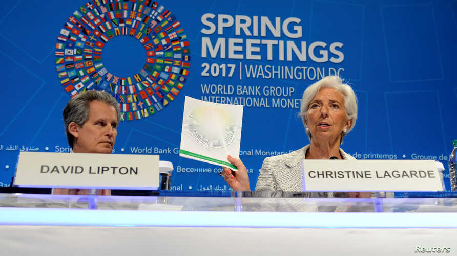 IMF Managing Director Christine Lagarde (R) holds up agenda papers as she attends a press briefing to open the IMF and World Bank's 2017 Annual Spring Meetings, with First Deputy David Lipton, in Washington, April 20, 2017.