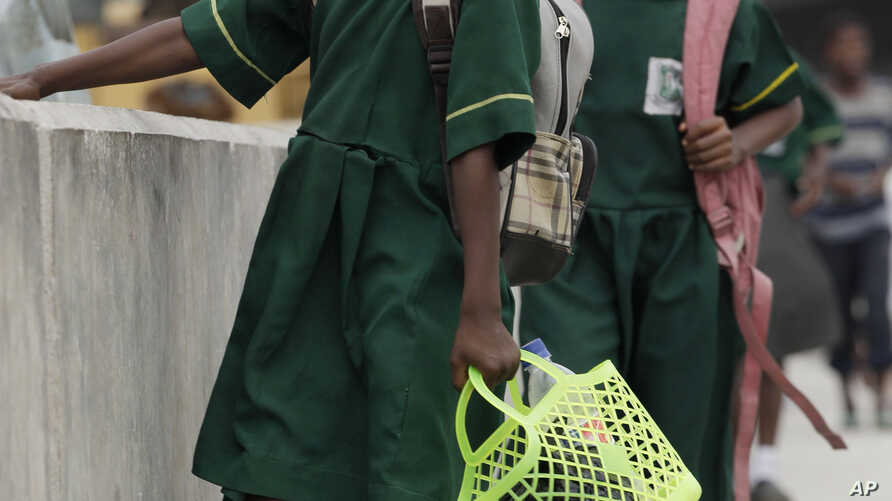 Young Nigerian school girls walk near a bus park. Often girls are forced to give up their education aspirations to get married, help family, (File Photo).