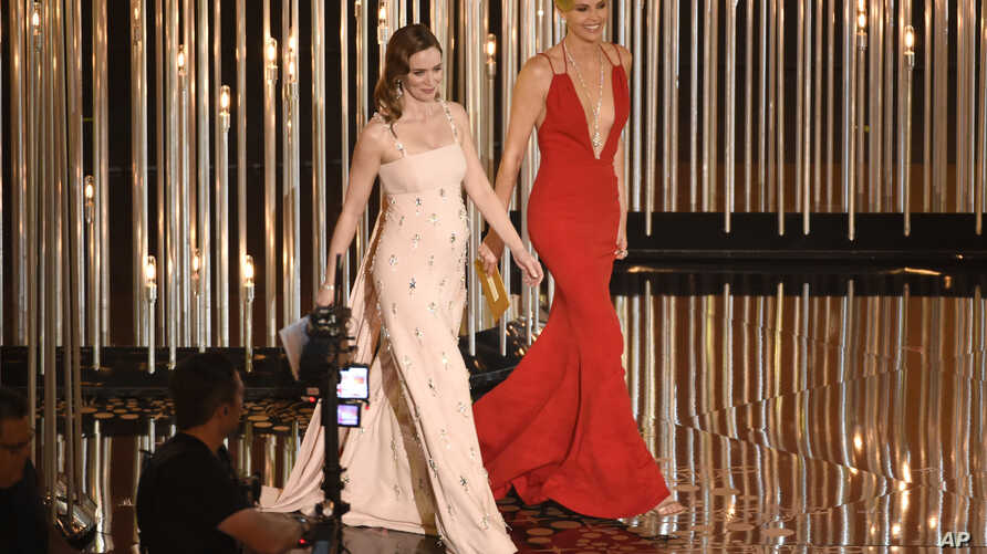 """FILE - Emily Blunt, left, and Charlize Theron present an award at the Oscars in Los Angeles, Feb. 28, 2016. The actresses appear in """"The Huntsman: Winter's War."""""""