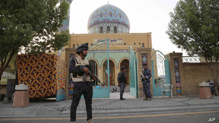 Iraqi security forces stand guard outside a Sunni mosque during the Muslim festival of Eid al-Fitr  in Baghdad, Iraq, July 17, 2015.