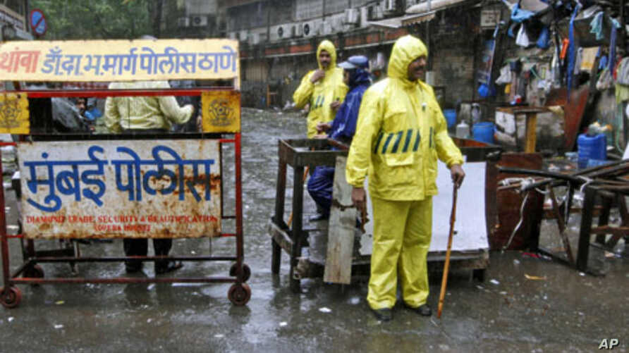 Policemen stand guard in the rain next to a barricade they installed at one of the sites of Wednesday's triple explosions, near the Opera House in Mumbai, July 14, 2011