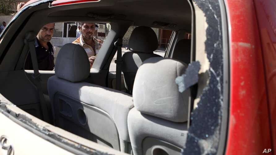 Iraqis inspect the scene of a car bomb attack in Baghdad, Sunday, Sept. 30, 2012.