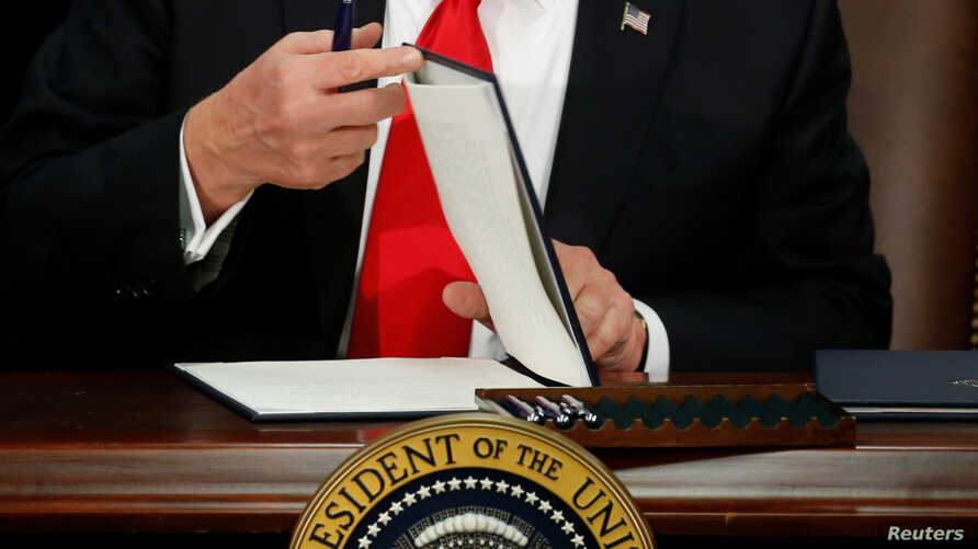 US President Donald Trump prepares to sign an executive order at Homeland Security headquarters in Washington, Jan. 25, 2017.