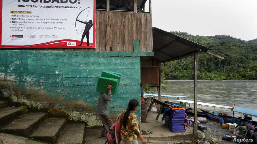 """People walk next to a warning sign at Atalaya port in the Alto Madre de Dios River, Peru, May 24, 2014. The sign reads, """"Watch out! Transit zone of indigenous in isolation."""""""