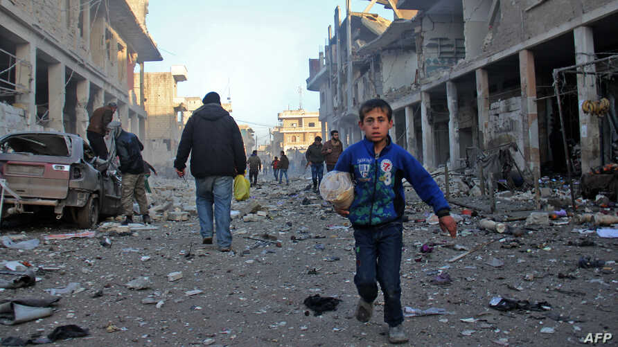A Syrian boy runs while carrying bread following a reported airstrike by government forces, in the Syrian town of Binnish, on the outskirts of Idlib.